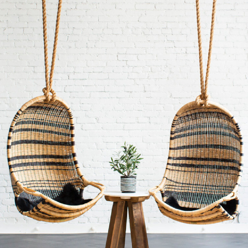 Two rattan hanging chair swings with black stripes and white brick wall at Grayson headquarters in LA - design by AR Interiors (Anna Rosemann). #hangingchair #modernrustic #chairswings
