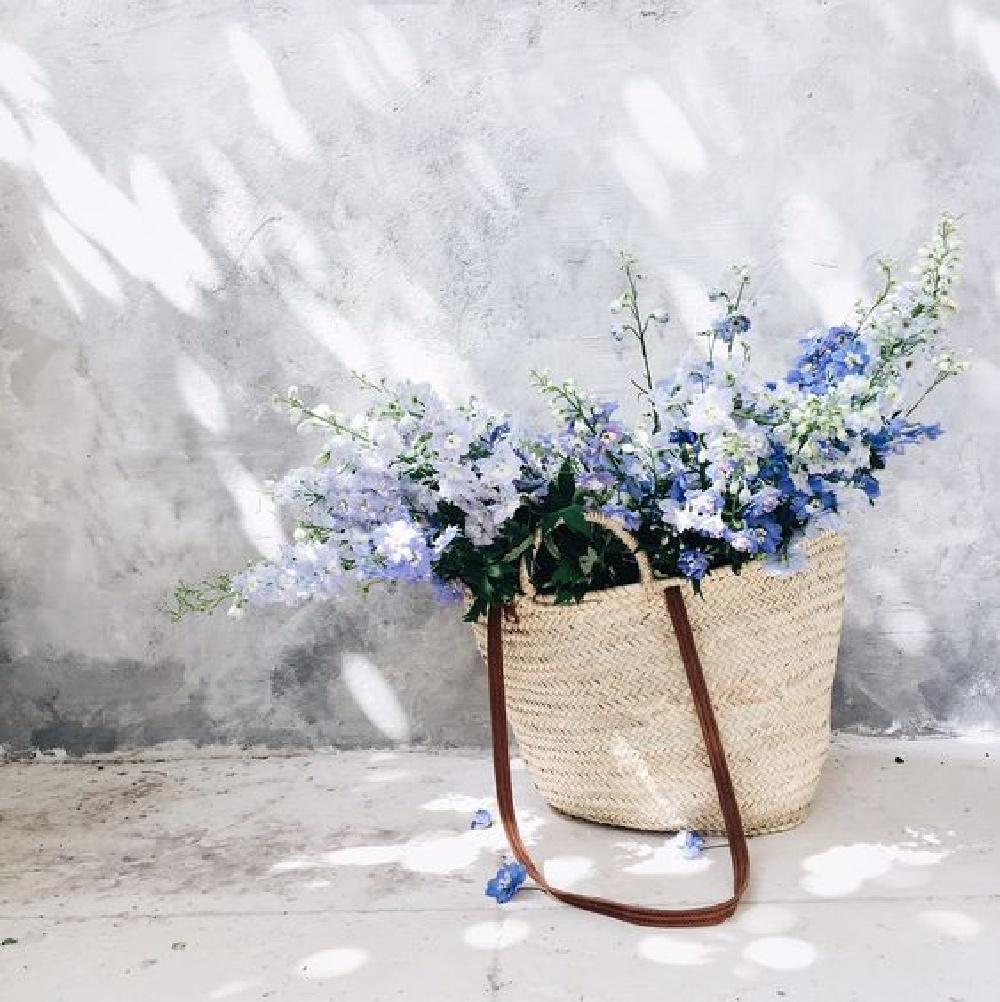 Beautiful French market basket filled with blue blooms - Vivi et Margot. #frenchcountrybasket #marketbasket