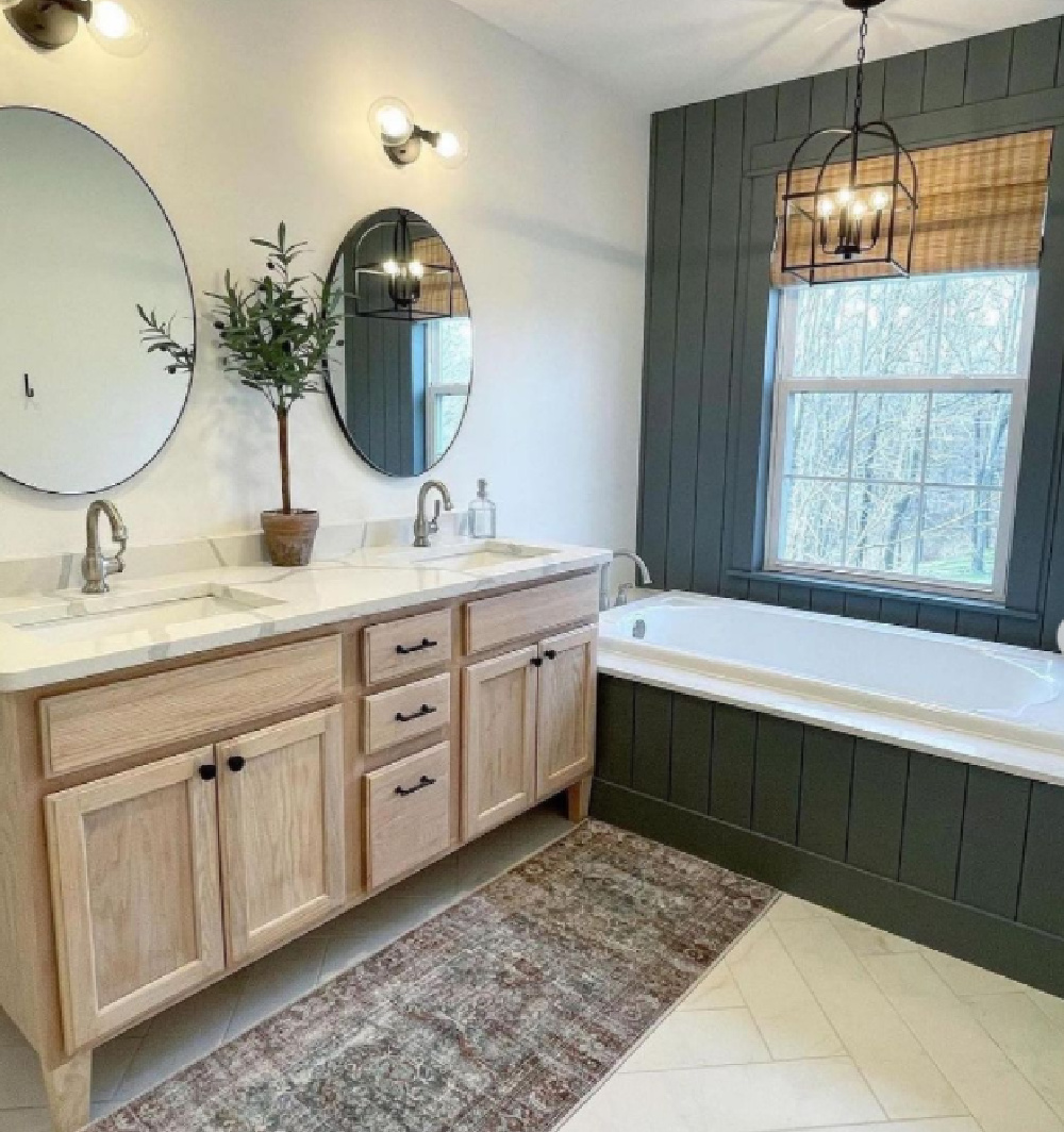 Remodeled bathroom with light wood vanity, round mirrors, and dark accent tub wall. (Before_and_After_Houses)