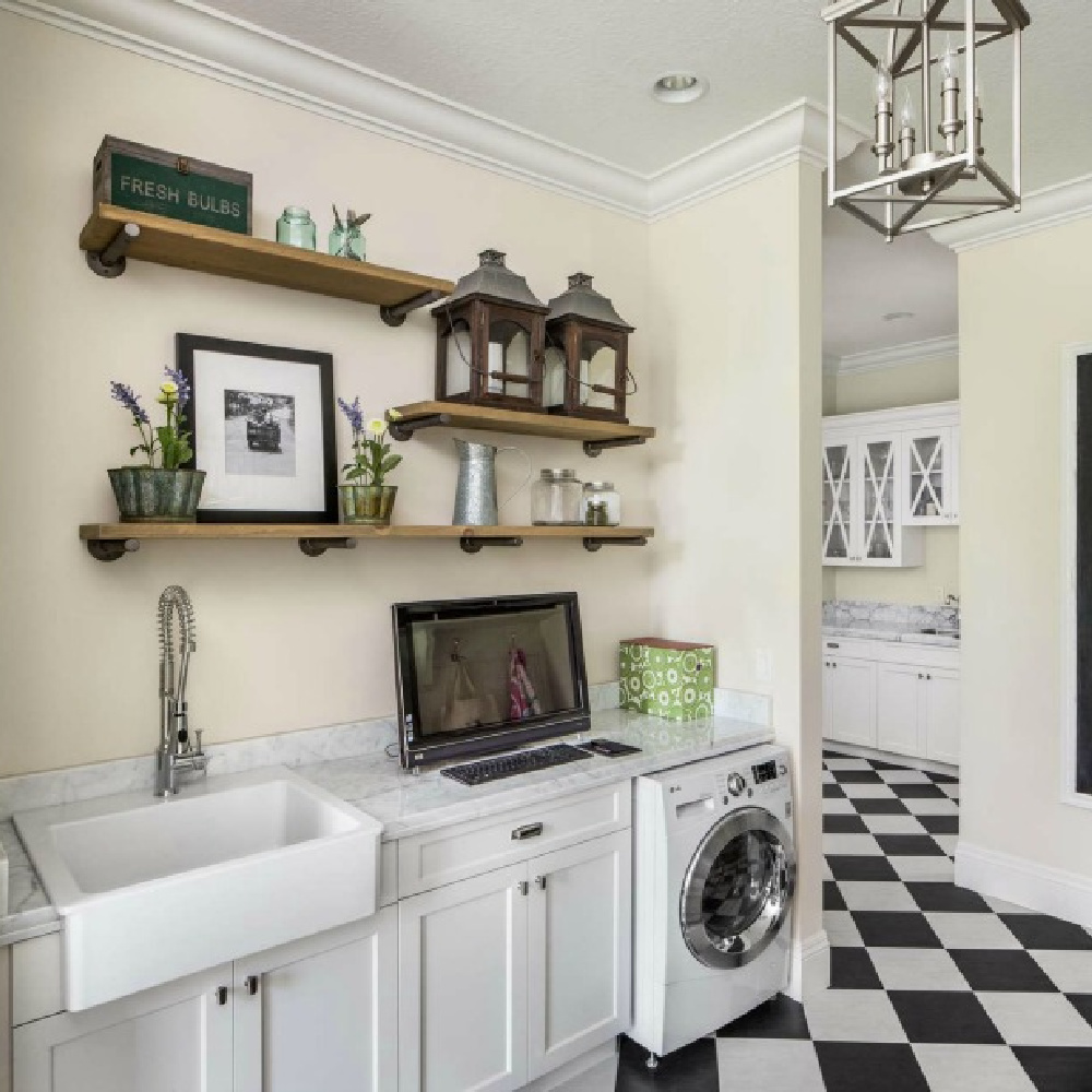 Traditional style laundry room with black and white check floor, farm sink, and decorative shelves - The Fox Group. #tratitionalstyle #laundryroom #interiordesign