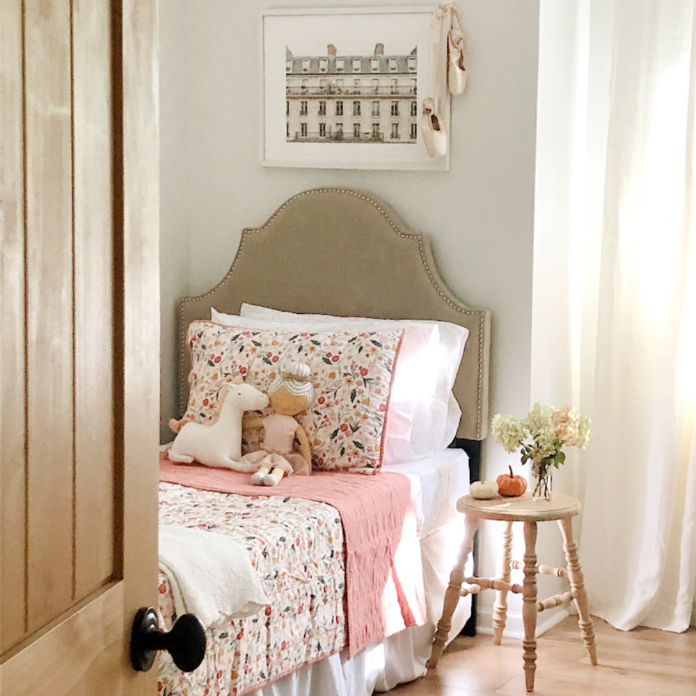 Hello Lovely's sweet girls bedroom with floral quilt, farmhouse stool as table and rustic alder door.