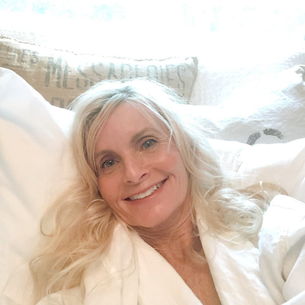 Michele of Hello Lovely Studio reclining on Nollapelli sheets in a white linen robe from Serena & Lily. #nollapellisheets #hellolovely #whitelinen #whitebedrooms
