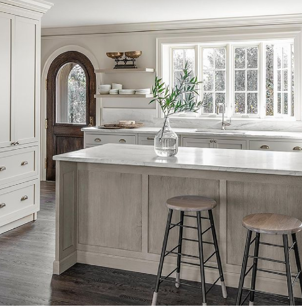 Minimal modern classic kitchen with subdued neutral palette, white trim, and arched door - Michael Del Piero. #nowallcabinets #kitchendesign