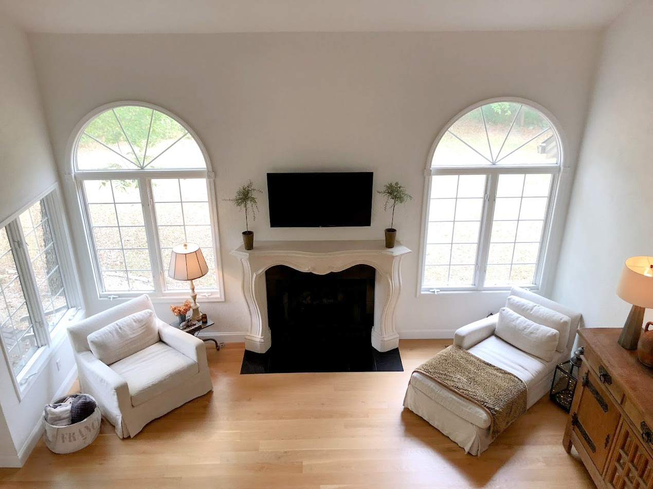 Hello Lovely's European country style living room with French inspired fireplace surround and white oak hardwoods.