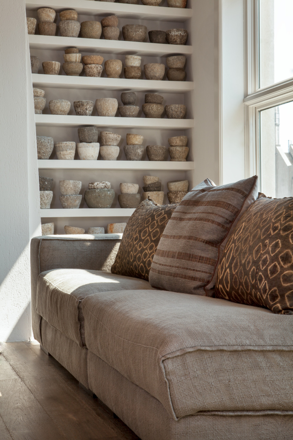 Shelves of artful antique Chinese mortars in a soulful space with design by Michael Del Piero.