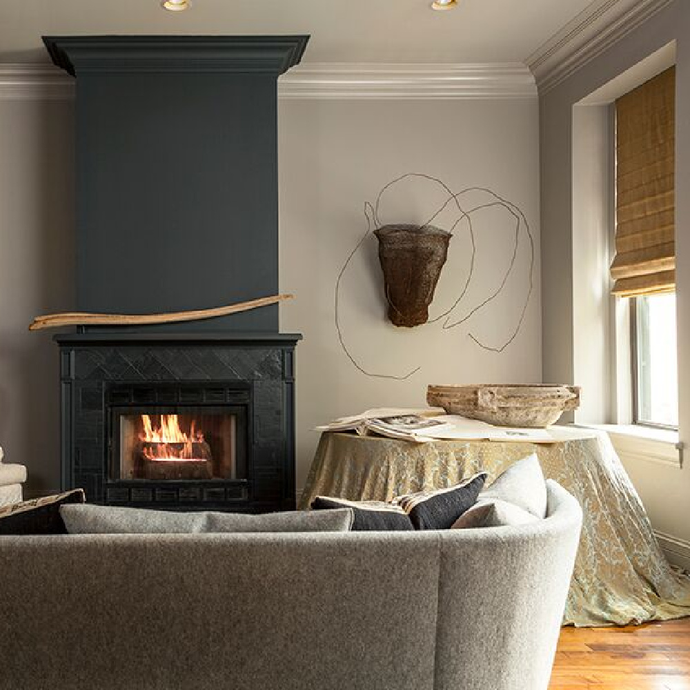 Black fireplace in a moody Chicago living room by Michael Del Piero.