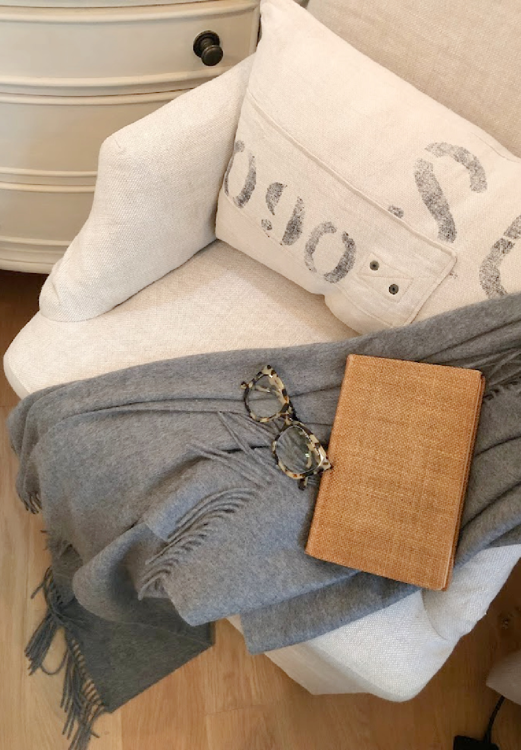 Warby Parker Aubrey frames for women on a dark gray cashmere throw on a linen chair in serene bedroom - Hello Lovely Studio.