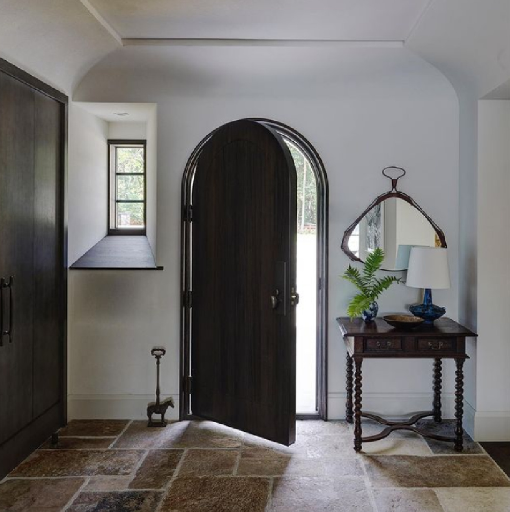 Breathtaking architecture in modern rustic entry with arched Old World door - interior design by Michael Del Piero.