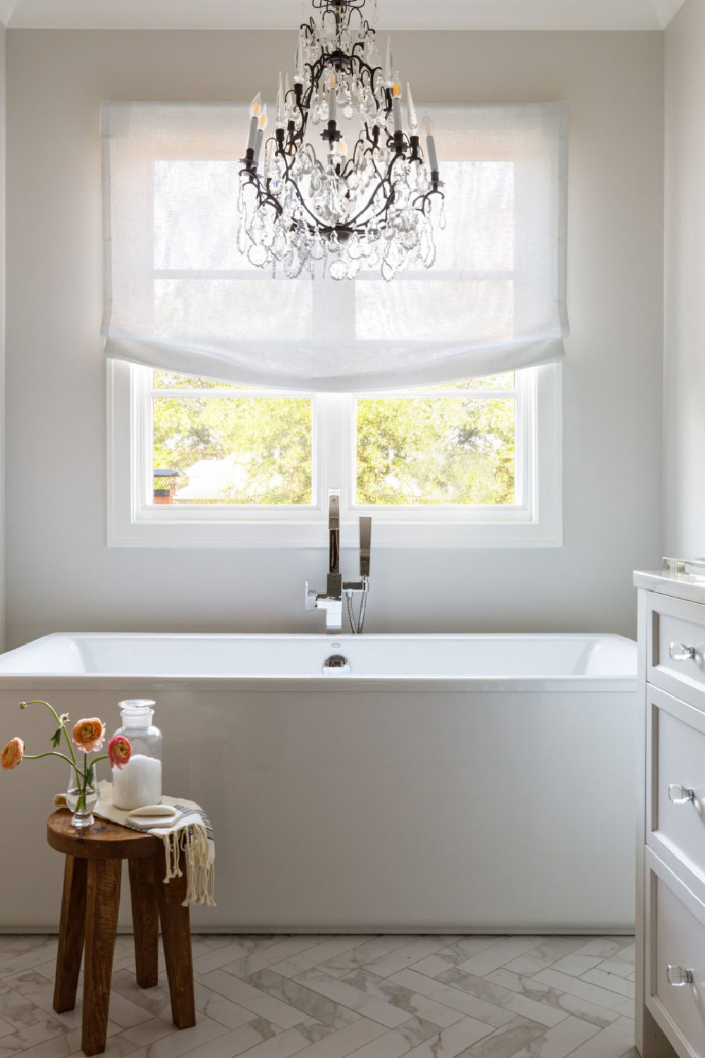 Serene and timeless white bath with soaking tub, crystal chandelier, and linen shade - design by Michael Del Piero.