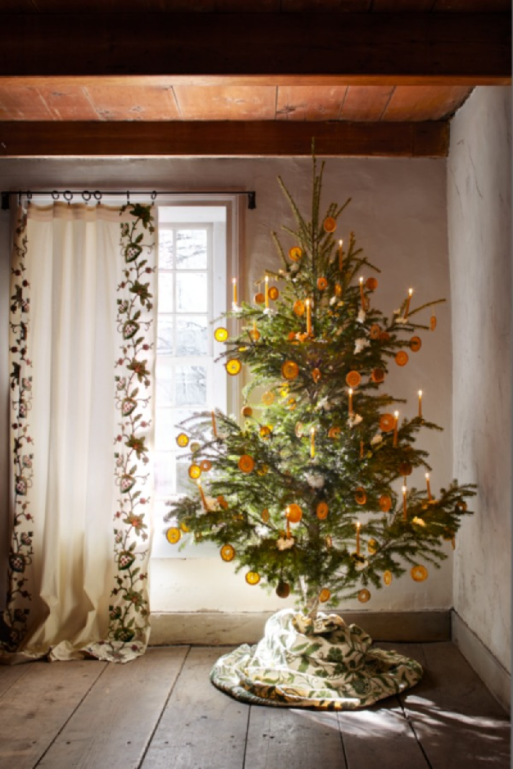 Dried orange garland on a Christmas tree. Floral designer Michael Putnam reimagined holiday décor with fresh blooms and artful twists on traditional topiaries, garlands, and wreaths within this 18th-century New York farmhouse - Veranda. #christmasdecor #christmastrees #scandinavian